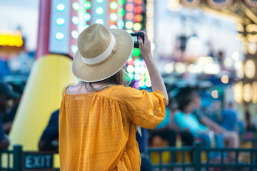 Woman taking picture at amusement park during her travel at summer vacation