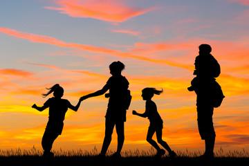joyful family silhouette at sunset