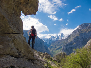 Woman hiker with backpack watching spectacular mountain landscape in Picos de Europa, Asturias, Spain