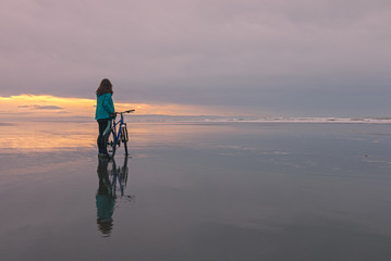 Young woman with a bicycle stands on ocean shore at sunset