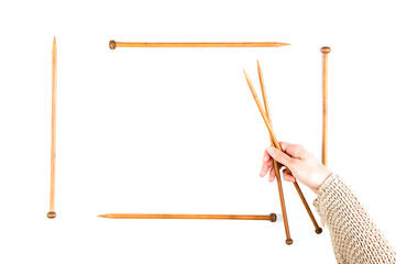 Knitting background. Woman hand and wooden knitting needles on white background