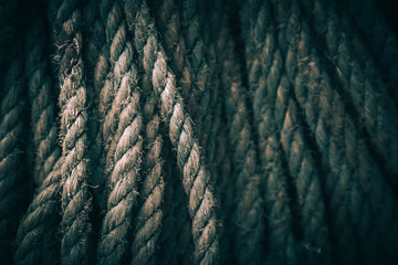 Dark background texture of coiled marine or nautical rope.Texture of synthethic mooring line. Close up