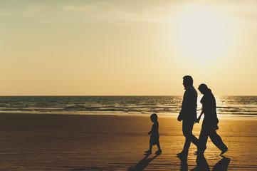 Family walks at sunset along the sea