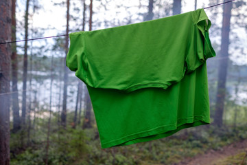 A green synthetic T-shirt is dried on a rope in the forest among the trees.