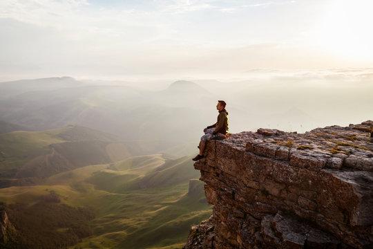 Man sitting on the cliff and enjoying sunset