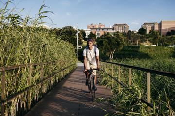Young man riding bike on pavement