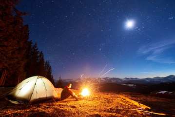 Garden Poster Brown Male tourist have a rest in his camp at night, sitting near campfire and tent under beautiful night sky full of stars and the moon and enjoying night scene in the mountains