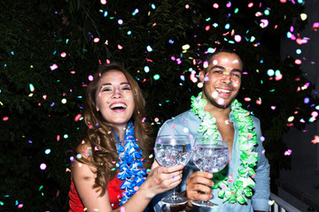 Cheerful man and woman clinking with glasses of cocktail and looking at camera happily in night.