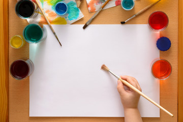 Preparing to drawing. Blank sheet among watercolors and brushes.Child's hand with brush above sheet