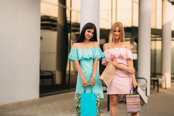 Beautiful girls go shopping. Sunny day. Summer