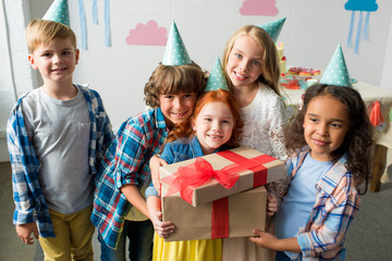 adorable happy multiethnic kids holding birthday presents and smiling at camera