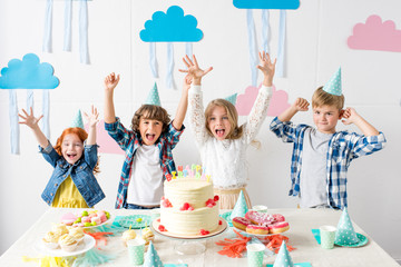 adorable happy kids raising hands and smiling at camera at birthday table
