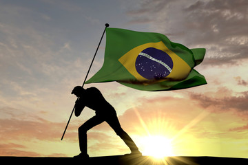 Brazil flag being pushed into the ground by a male silhouette. 3D Rendering Wall mural