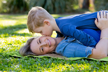 Young son kissing Mother whilst playing on rug in park