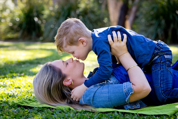 Mother and young son embracing and about to kiss whilst playing
