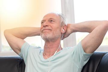 Portrait of mature man listening music with earphones, light effect