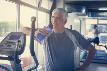 The elderly man holding a bottle of water. The man is refreshed water after exercise at the gym. Man workout in gym.