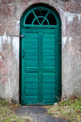 A weathered concrete outdoor underground cellar with green wooden door for food storage.
