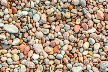 Many round and smoth colorful pebbles seen from above.
