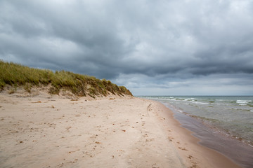 Dark clouds and stormy weather over beautiful island beach with grass and water with waves.