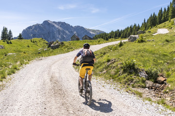Mountainbiker in Carnic Alps with view to mountain Rosskofel