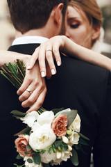 Bride crosses her tender hands on groom's back