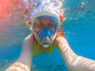 Snorkel girl underwater selfie. Snorkeling in full face mask. Summer activity.
