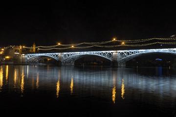 Iluminación nocturna del hermoso puente de Triana en la ciudad de Sevilla, España