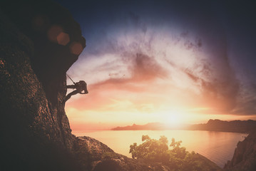 Climber on a rock against sunset. Instagram stylization