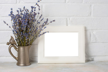 White wooden frame with copyspace and lavander in eco rustic style on white Brick wall background.