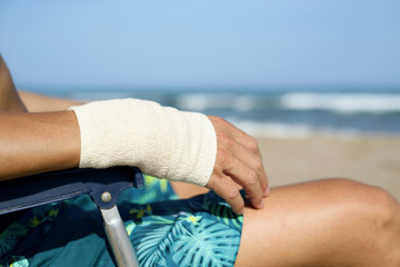 man on the beach with a bandage in his wrist