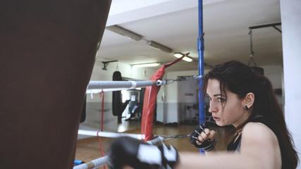 Beautiful female boxer training punching bag in boxing gym. Self defense workout. Motion blur effect.