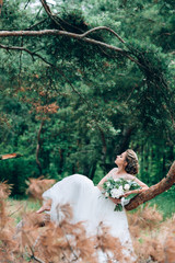 Beautiful bride in the nature in a luxurious dress