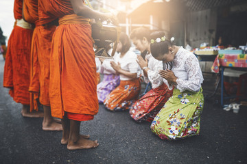 Thai woman pay homage to a Buddhist monk in morning.