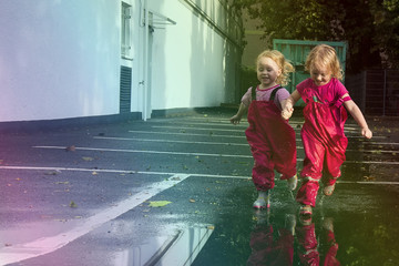 Children play on the street after the rain in pink bright rubber boots. The rays of the sun are reflected in the drops of water