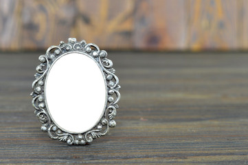 Empty baroque picture frame on wooden background