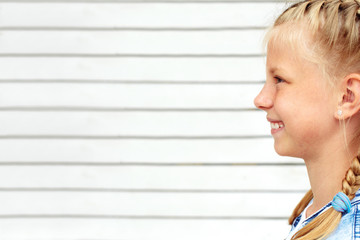 Portrait of a cute girl in profile on a white wooden wall background