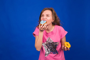 Young beautiful woman eating doughnuts on blue background. Unhealthy diet, junk food and food addiction concept