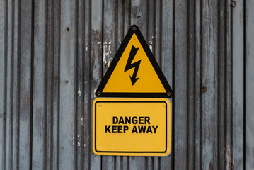 Danger electricity sign on grungy wooden door background