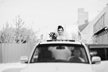 Portrait of a flawless bride looking out of the sunroof in the wedding car. Black and white photo.