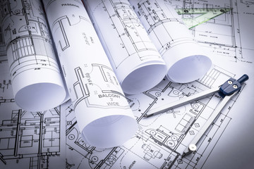 Architectural blueprints and blueprint rolls and a drawing instruments on the worktable. Drawing compass, plans. Civil Engineering, Construction background.