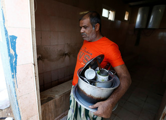 Expatriate worker carries kitchen utensils as he walks in his accommodation in Riyadh