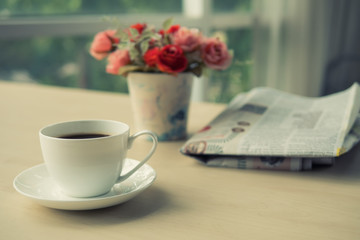 Cup of coffee with newspaper on the table in the morning , warm tone background