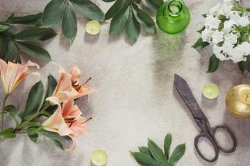 Creative female table with candles, scissors and flower. Top view with copy space.