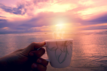 Hand holding coffee cup at the beach in sunset time.