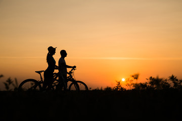 Boy and girl with their bicycles watching a dramatic sunset over a rural field