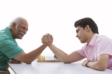 Grandfather and grandson doing arm wrestling