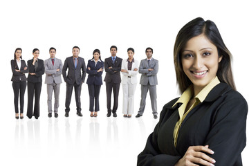 Portrait of businesswoman smiling with businesspeople in background
