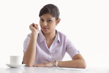 Portrait of confident businesswoman sitting at her desk