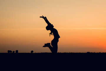 Joyful girl jumping at sunset. Silhouette